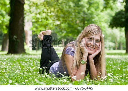 Young smiling woman lying in grass during sunny day (park - outdoors)