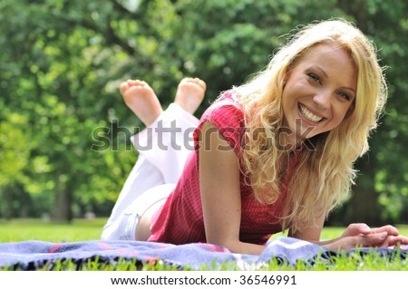 Young smiling woman lying on rug in grass during sunny day (park - outdoors)
