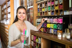 young smiling woman picking multicolored candles in craft department