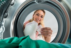 Young Smiling Woman Pouring Detergent In A Lid From Inside The Washing Machine