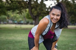 Young smiling woman resting after an active fitness training outdoor. Happy latin girl in sportswear resting after run at park. Portrait of curvy woman jogging at park with copy space.