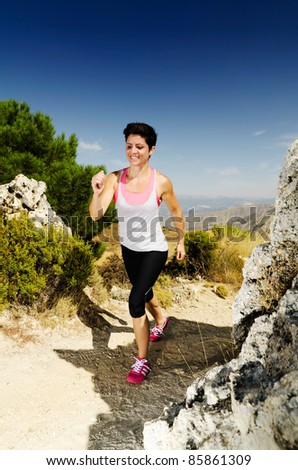Young smiling woman running on a dry mountain path.