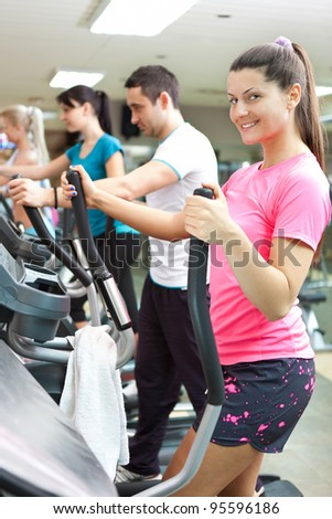 young smiling woman running on the treadmill with other people on background