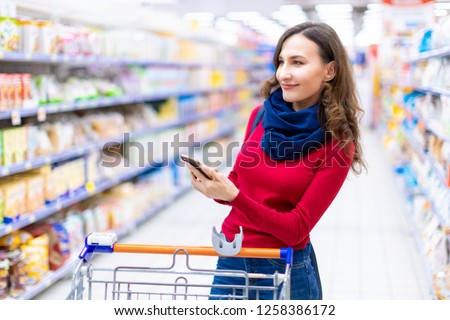 Young smiling woman shopping in a supermarket looking at the screen of the phone her shopping list (grocery list) - consumerism and choosing concept