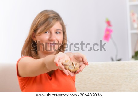 Young, smiling woman showing her new deaf aids on her hands