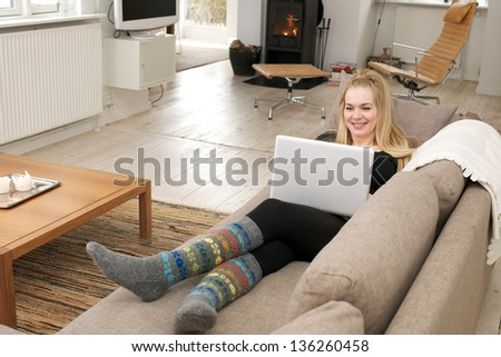 Young smiling woman, sitting in a couch, working on her laptop