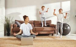 Young smiling woman sitting in lotus pose with laptop on floor and calming down while noisy kids jumping around in living room