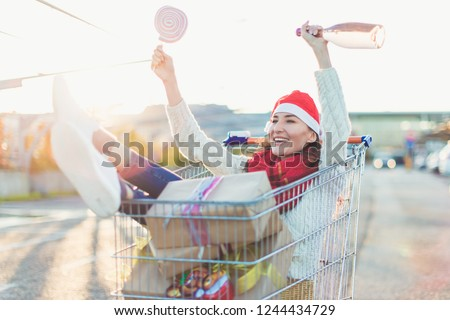 Young smiling woman sitting in shopping cart with a lot of gift boxes and pink marshmallow roller pop and a bottle of rosé sparkling wine in her hands wearing red Santa Christmas hat  #1244434729