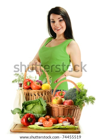Young smiling woman standing at the table with variety of fresh raw vegetables in wicker baskets isolated on white