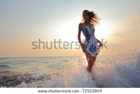 Young smiling woman standing in sea waves and holding her dress