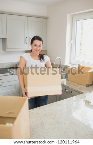 Young smiling woman standing in the kitchen while holding a moving box