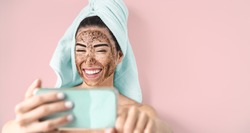 Young smiling woman taking selfie while doing coffee scrub facial mask - Happy girl having skin care spa day at home - Healthy alternative natural exfoliation treatment and technology concept