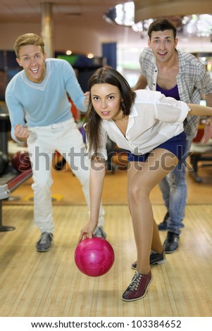 Young smiling woman throws ball in bowling; tow men support her; shallow depth of field