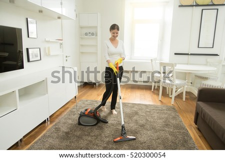Young smiling woman vacuum cleaning the carpet in the living room, modern scandinavian interior. Busy, cleaning day. Home, housekeeping concept