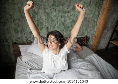 Young smiling woman waking up happy after healthy sleep stretching on comfortable bed with sleeping man at background, rested refreshed girl enjoys pleasant wakeup, good morning in cozy loft bedroom