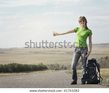 Young smiling woman with backpack catching a car on empty road