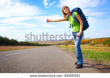Young smiling woman with backpack hitch hiking on an asphalt road