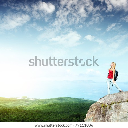 Young smiling woman with backpack standing on cliff's edge and looking to a sky