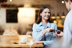 Young smiling woman with card holding it over payment terminal while paying for her order in cafe