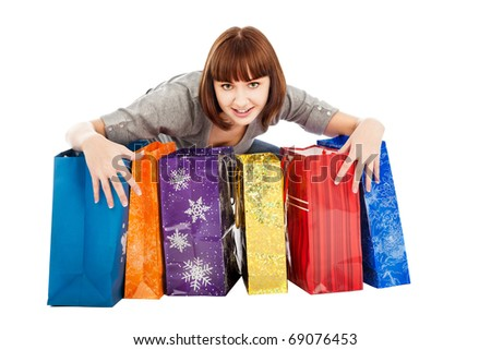 Young smiling woman with colored shopping bags, isolated on white