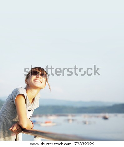 Young smiling woman with glasses outdoor portrait on blue airy background with copyspace