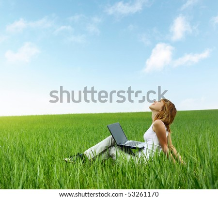 Young smiling woman with laptop sitting in meadow with green grass