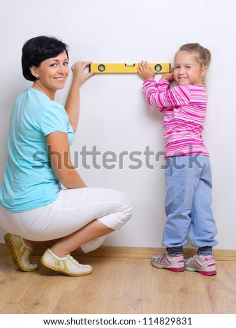 Young smiling woman with little girl and measurement level
