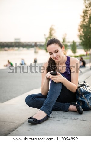 Young smiling woman with mobile phone ( touchscreen smartphone)