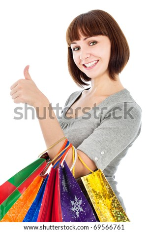 Young smiling woman with shopping bags make her thumb up, isolated on white
