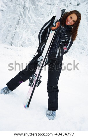 Young smiling woman with skis standing on the mountain.
