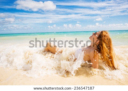 young smiling woman with sunglasses laying on beach covered in ocean waves on tropical blue sea sky background. Paradise getaway nature destination travel vacation concept. Positive face expression