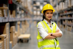 Young smiling woman worker and vest checking box in stock in  factory warehouse, Staff check stock girl prepares shipping goods and packaging products to customer.