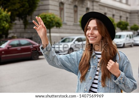 Young smiling young European woman walks outdoor, waves hand as notices friend into distance, strolls across street, wears stylish black headgear and denim jacket, poses over urban background.