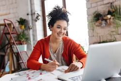 Young smilng woman with dark curly hair sitting at the table happily working on laptop drawing fashion illustrations spending time in modern cozy workshop with big windows