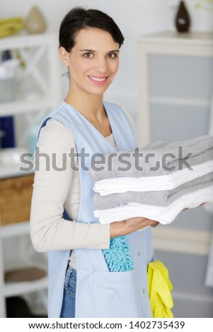young smily housekeeper with towels #1402735439