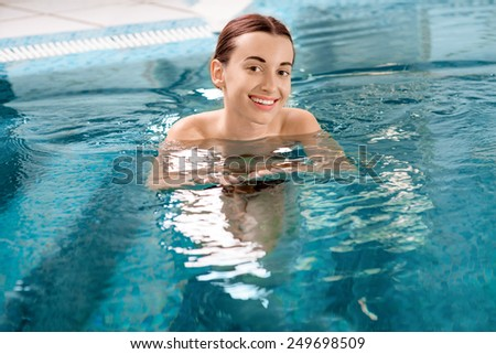 Young smling woman swimming in the swimming pool at the hotel spa