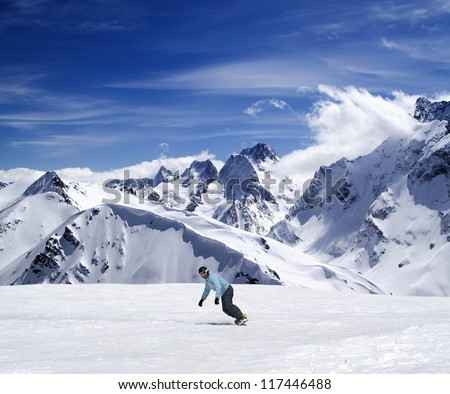 Young snowboarder on ski slope in high mountains