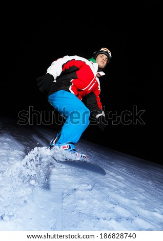 Young snowboarder sliding at night