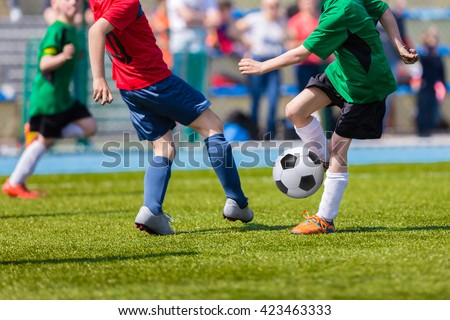 Young soccer football players playing match at sports field. Football soccer match for children. Kids playing soccer game tournament cup. Physical education classes at school.