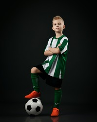 Young soccer player, football school student, kid boy in red white striped uniform stands holding arms crossed and with ball under his foot over black background. Side view