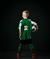 Young soccer player, football school student, teenager boy in red white striped uniform stands back to camera holding ball over black background. Back view