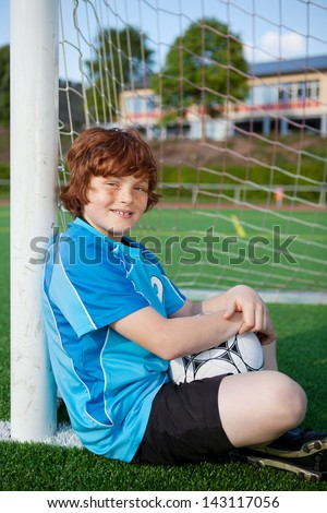 young soccer player having a break and leaning at soccer goal