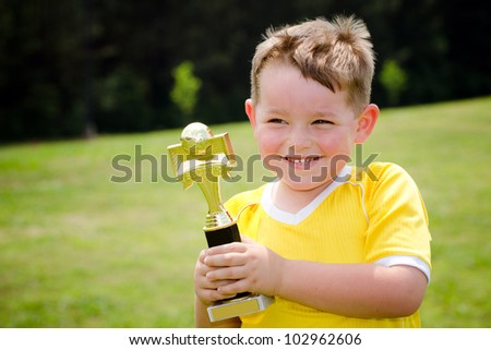 Young soccer player in uniform with his new trophy