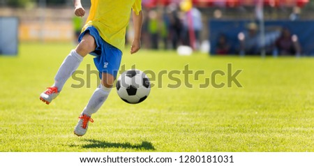 Photo of Young Soccer Player Kicking Ball. Horizontal Football Match Image with Blurred Pitch in the Background