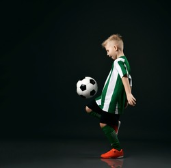 Young soccer player, kid boy in red white striped uniform shirt, shorts, stockings and sneakers is hitting the ball with knee over black background. Side view