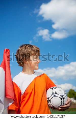 young soccer player standing against blue sky