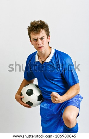 Young soccer player whit ball against grey background