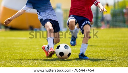 Young Soccer Players Competition. Boys Kicking Football Ball. Soccer Youth Teams Play Outdoor Tournament. Soccer Stadium in the Background