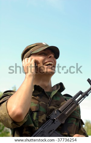 young soldier calling on a phone and smiling