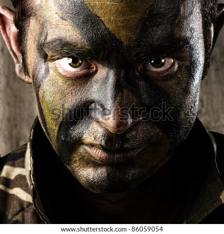 young soldier face looking straight ahead against a a grunge wall